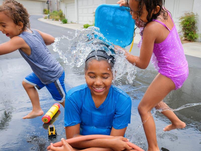 Våt syskongrupp som utanför spelar med vatten fotografering för bildbyråer