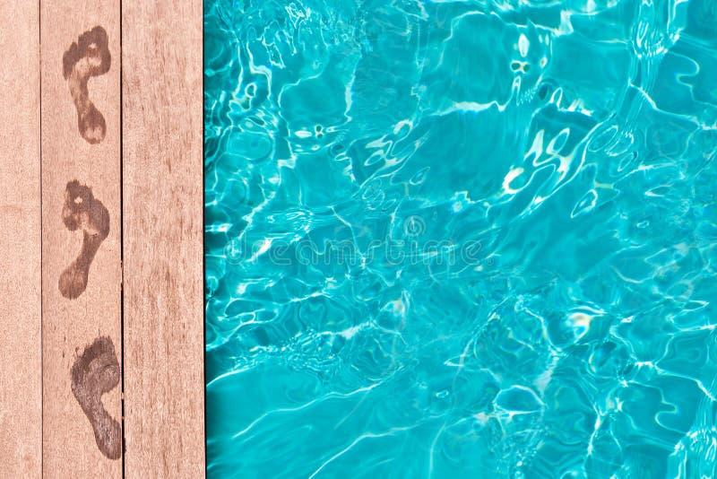 Våta fotspår på däcket av en simbassäng arkivfoton
