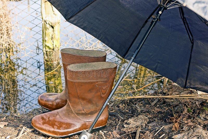Våta gummistöveler under paraplyet royaltyfri fotografi