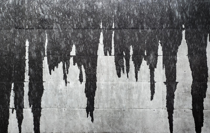 Våta istappar på fasadväggen som skapar grå bakgrundstextur för abstrakt begrepp royaltyfria foton