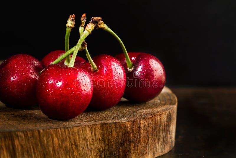 Våta körsbär på ett träkökbräde royaltyfri foto