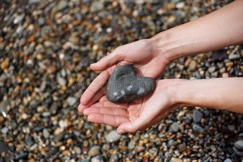 Våta kvinnlighänder med en sten i form av en hjärta royaltyfri bild