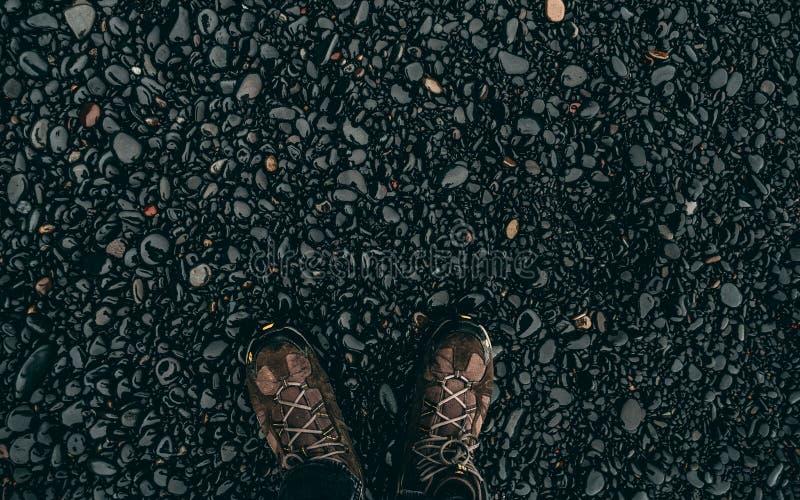 Våta svartstenar med att fotvandra skor i Island fotografering för bildbyråer