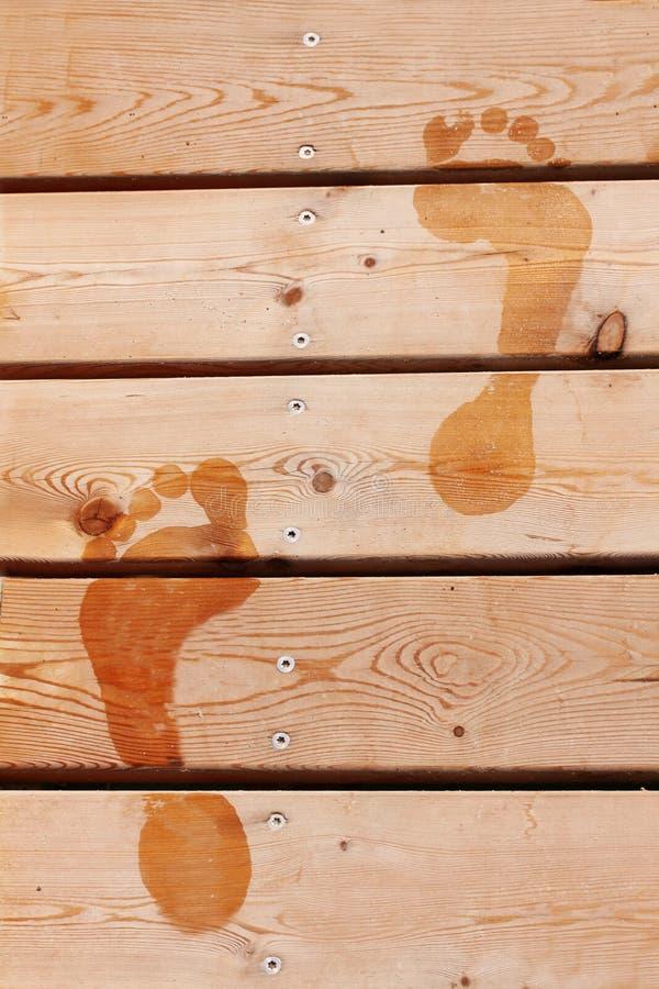 Våta tryck av två mänskliga fot på brunt trädäckgolv close upp arkivbilder