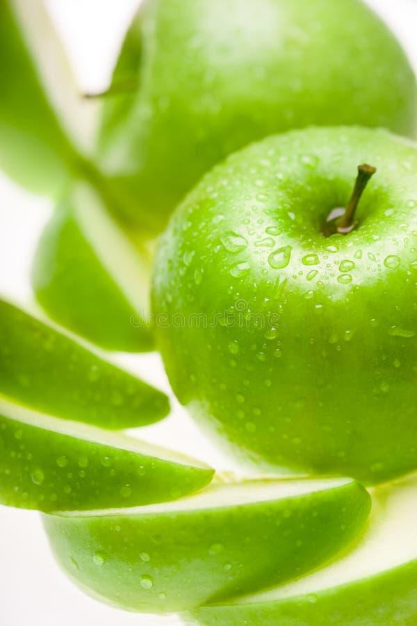 Vått äpple för gräsplan med skivor på vit bakgrund royaltyfria bilder