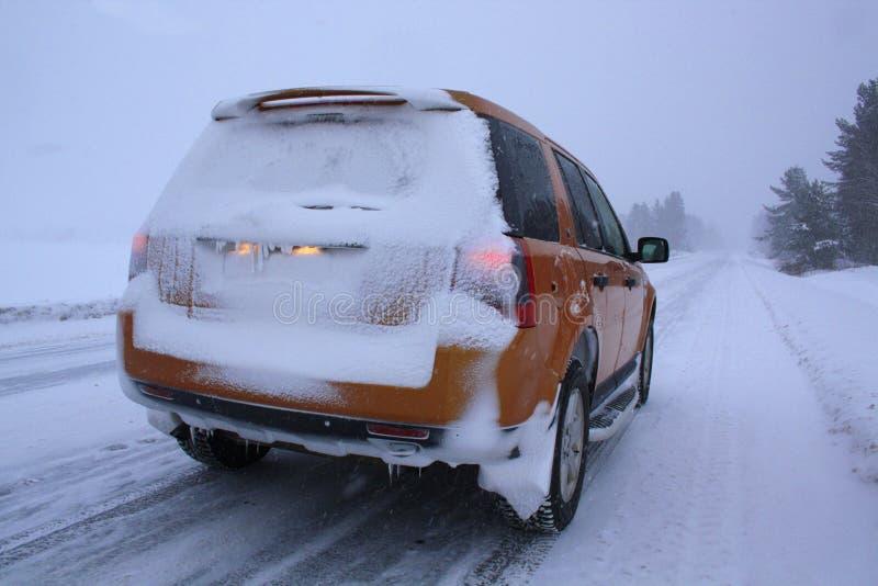 Véhicule avec la neige sur la route de l'hiver photo stock