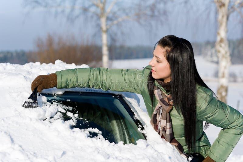 Véhicule de l'hiver - la femme enlèvent la neige du pare-brise image libre de droits