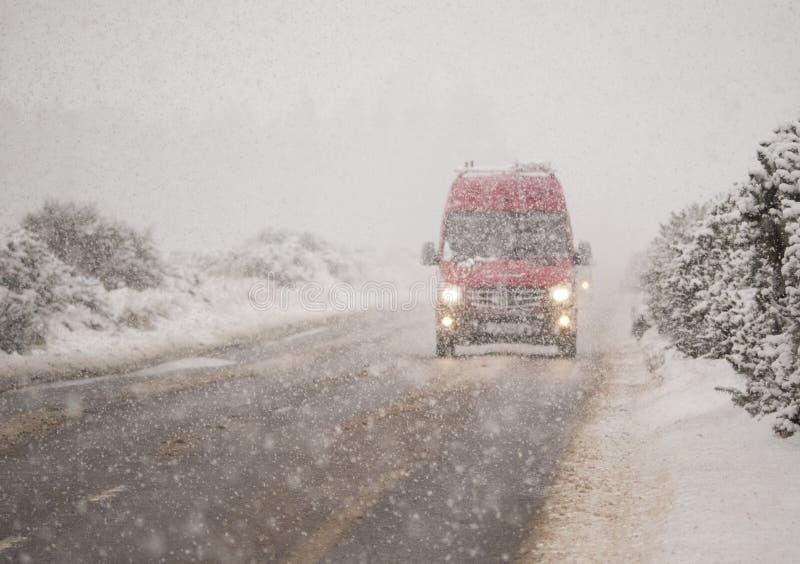Véhicule de livraison rouge dans la chute de neige importante photos stock
