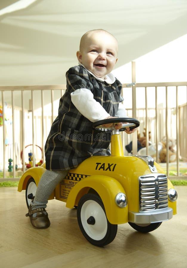 Véhicule de sourire de jouet d'équitation de chéri images stock