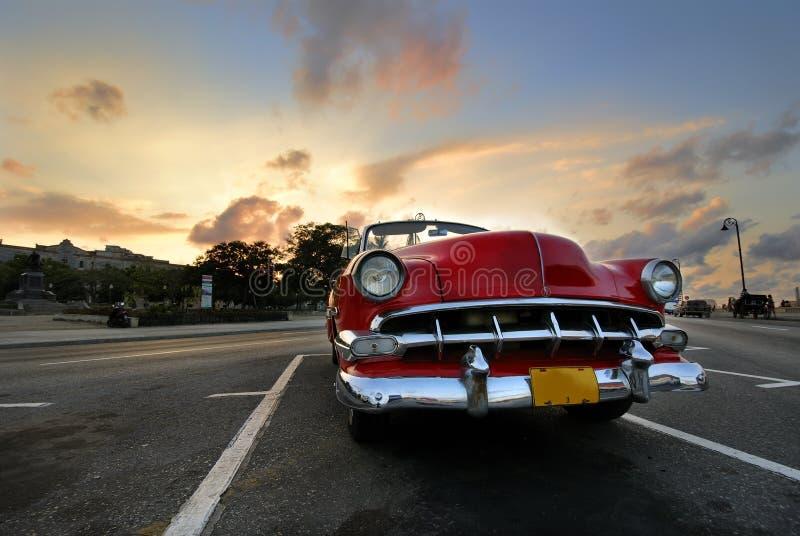 Véhicule rouge dans le coucher du soleil de La Havane image libre de droits