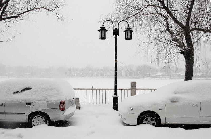 Véhicules dans la neige près du lac photo stock