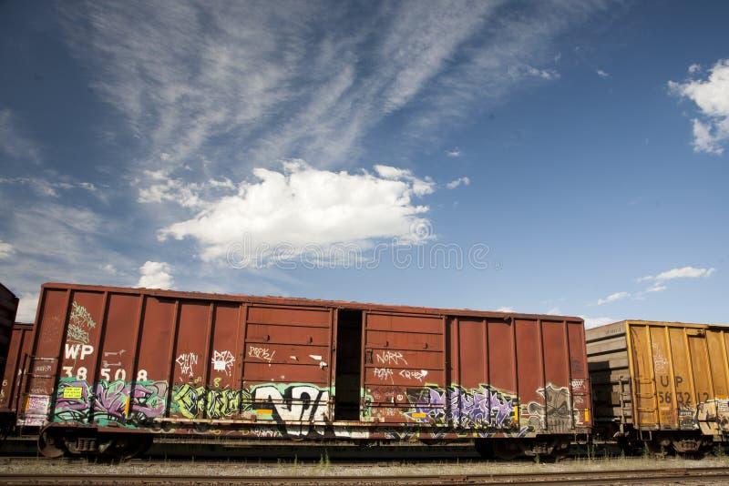 Véhicules de train avec le graffiti contre un ciel bleu photographie stock libre de droits