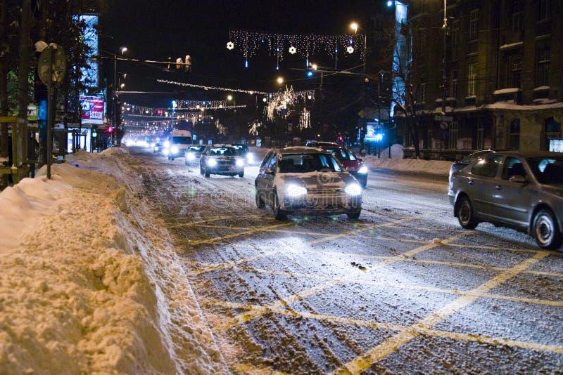 Véhicules sur la route neigeuse à Bucarest images libres de droits