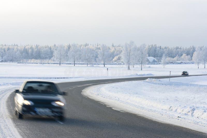 Véhicules sur une route de l'hiver images stock
