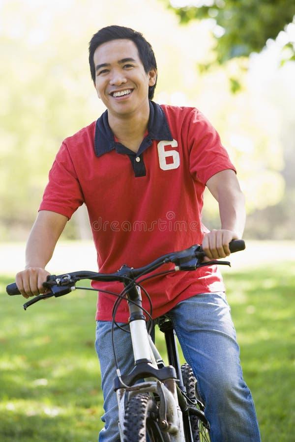 Vélo asiatique d'équitation d'homme en stationnement photos stock