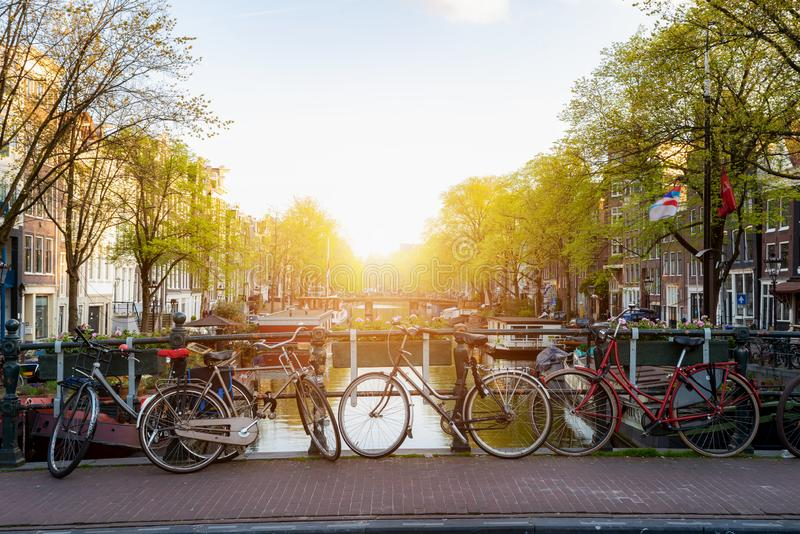 Vélo au-dessus de ville d'Amsterdam de canal aux Pays-Bas avec la vue sur la rivière Amstel pendant le coucher du soleil images stock