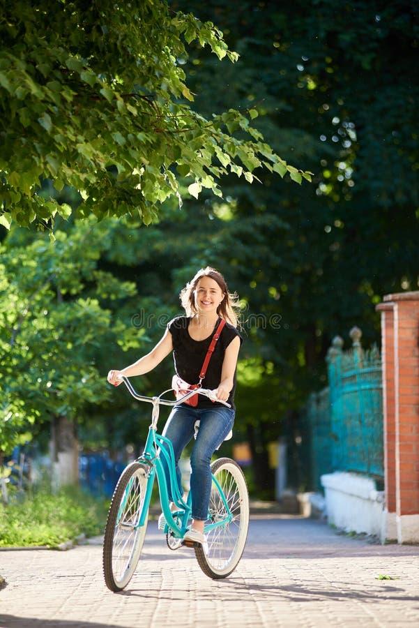 Vélo bleu de sourire d'équitation femelle en parc le jour d'été photo stock