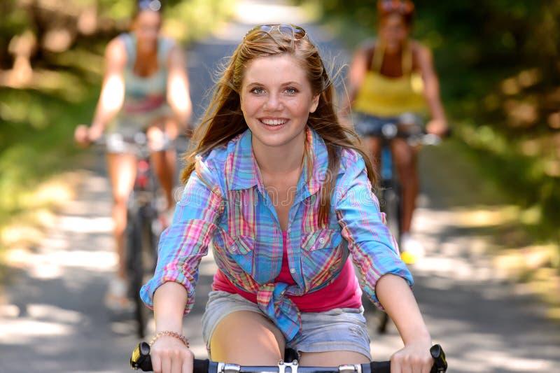 Vélo d'équitation d'adolescente avec des amis images stock