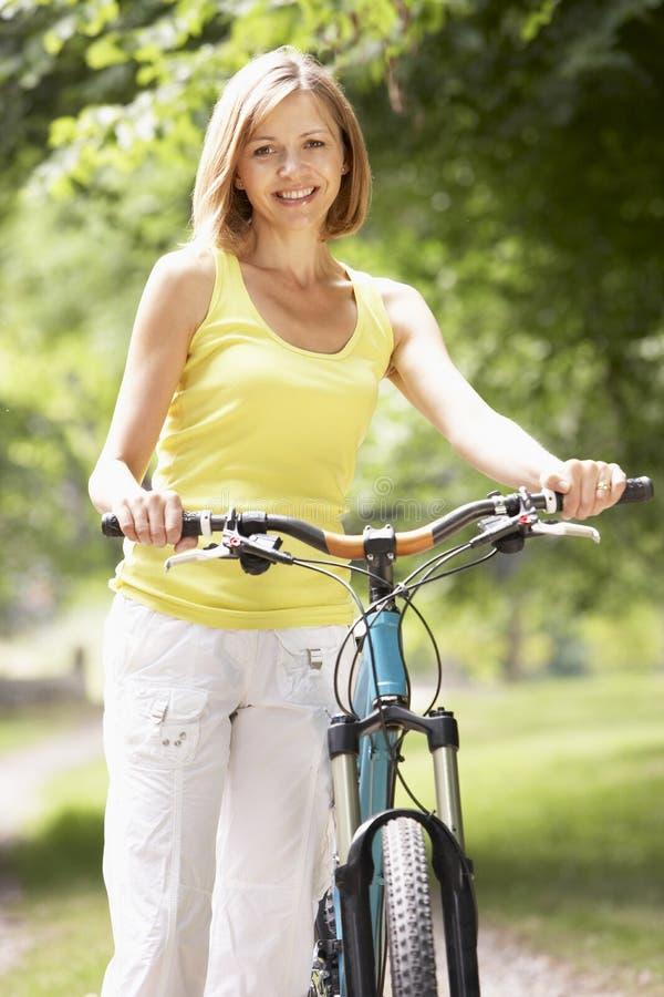 Vélo d'équitation de femme dans la campagne photographie stock