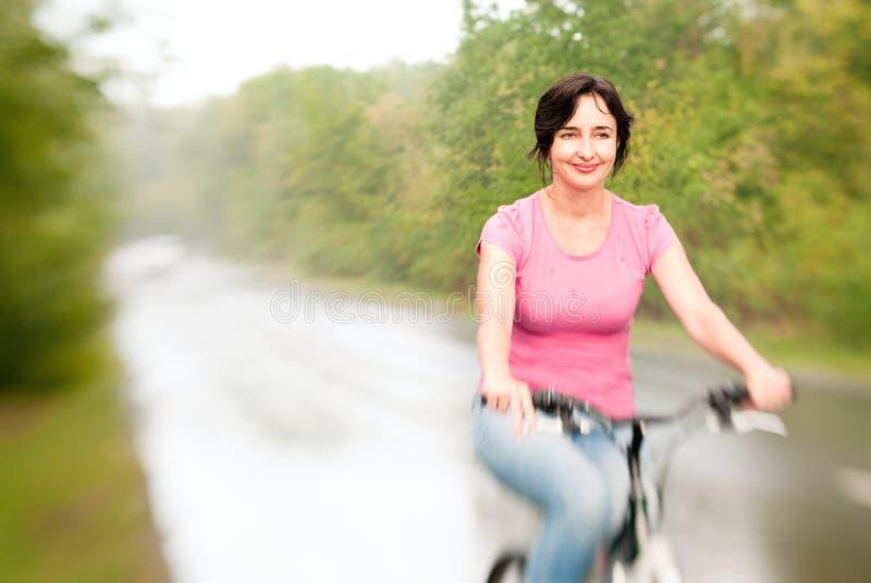 Vélo d'équitation de femme sur le pluvieux photos stock