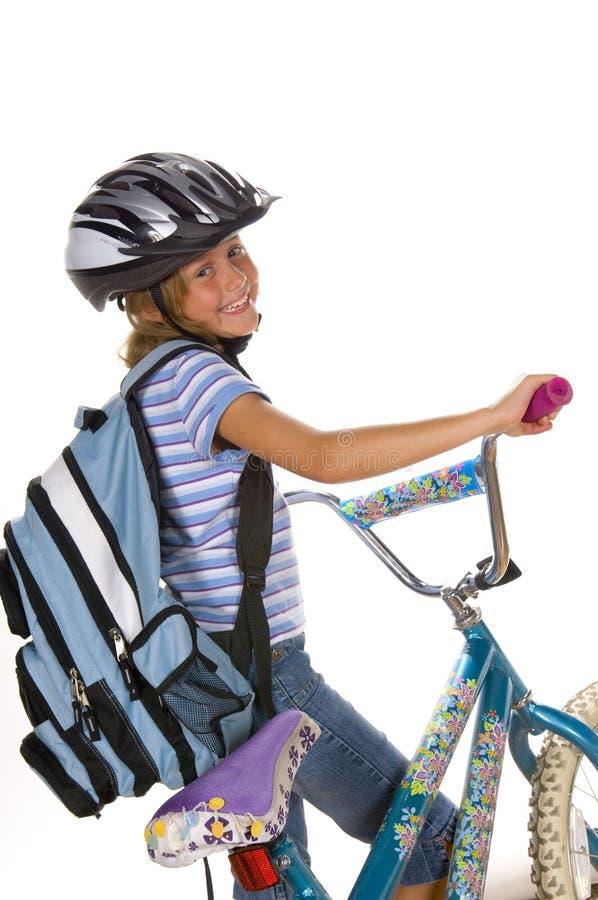 Vélo d'équitation de fille à l'école photographie stock libre de droits