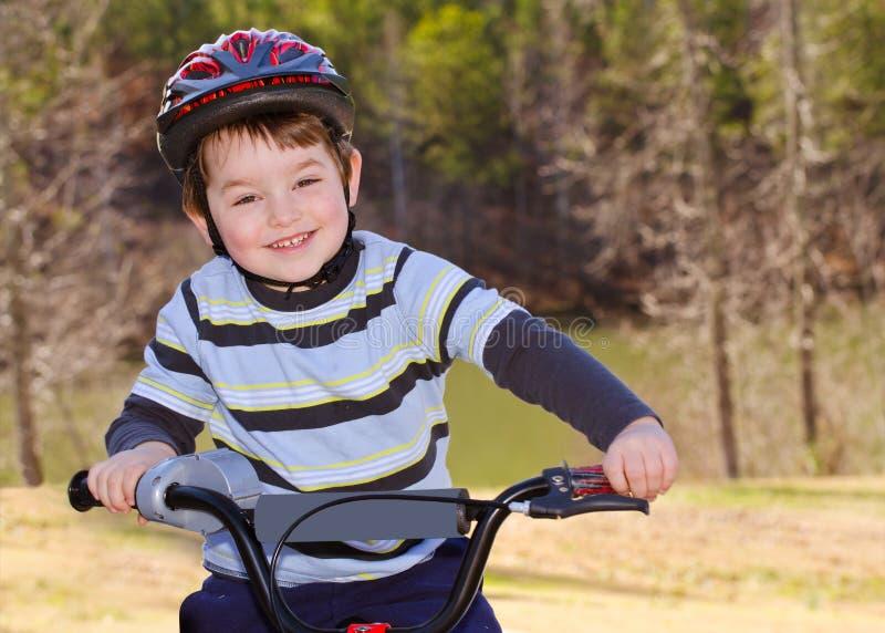 Vélo d'équitation de garçon avec le casque de sécurité image libre de droits