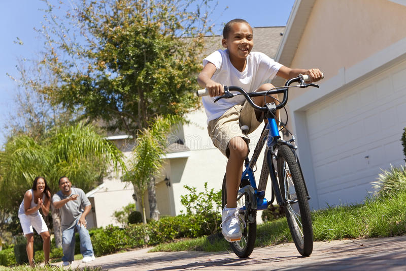 Vélo d'équitation de garçon d'Afro-américain et parents heureux photographie stock libre de droits