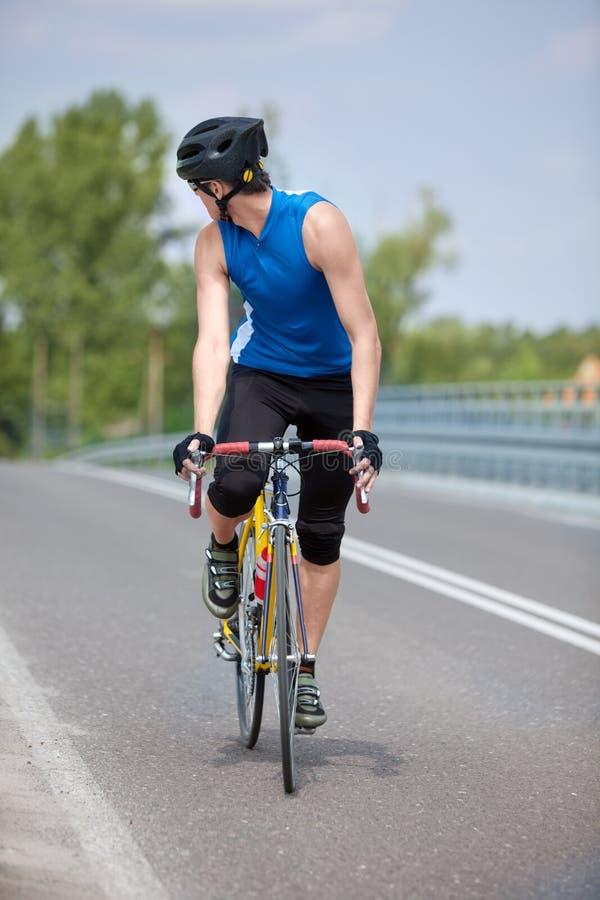 Vélo de chemin de cycliste regardant derrière image stock