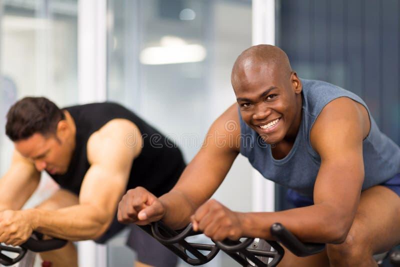 Vélo de gymnase d'hommes photos stock