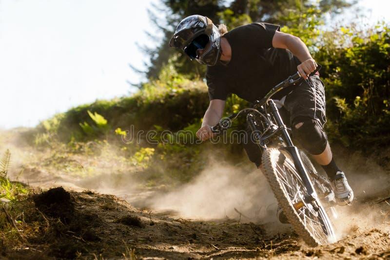 Vélo de la poussière de Mountainbiker en descendant image stock
