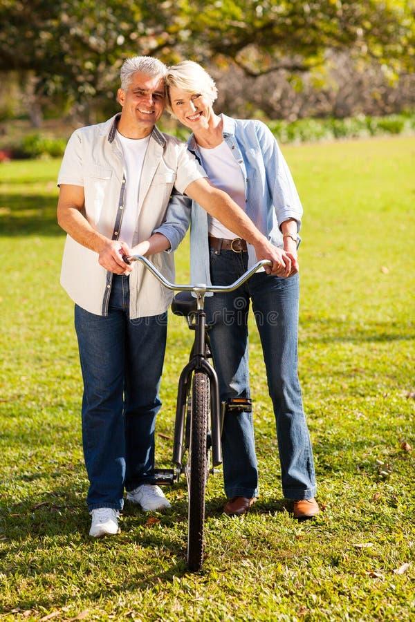 Vélo de marche de couples photo stock