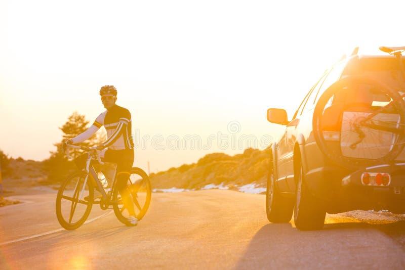Vélo de montagne d'équitation d'homme de cycliste au coucher du soleil photos libres de droits