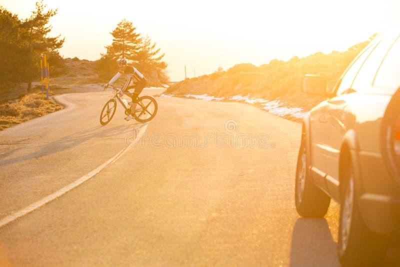 Vélo de montagne d'équitation d'homme de cycliste au coucher du soleil photos stock