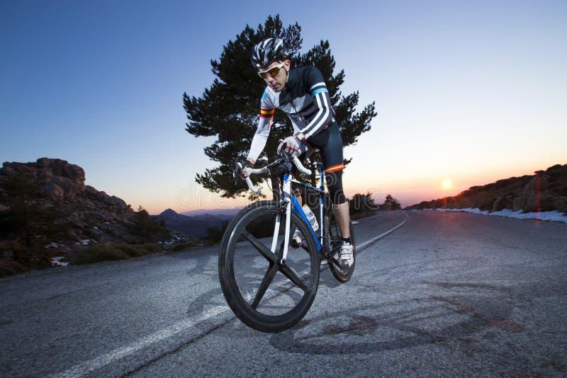 Vélo de montagne d'équitation d'homme de cycliste au coucher du soleil images stock