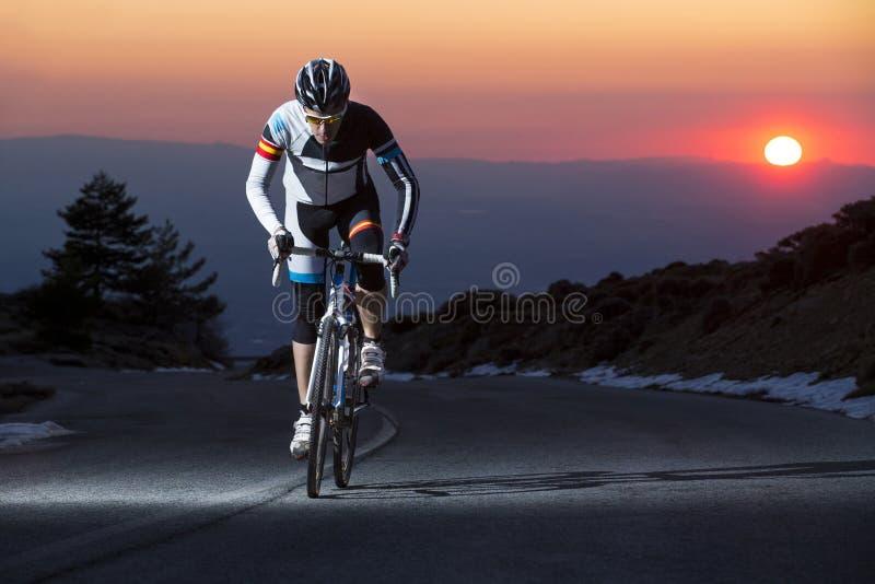 Vélo de montagne d'équitation d'homme de cycliste au coucher du soleil images libres de droits
