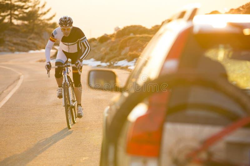 Vélo de montagne d'équitation d'homme de cycliste au coucher du soleil sur une route de montagne images libres de droits