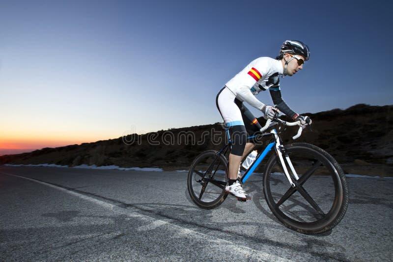 Vélo de montagne d'équitation d'homme de cycliste au coucher du soleil sur une route de montagne photo stock