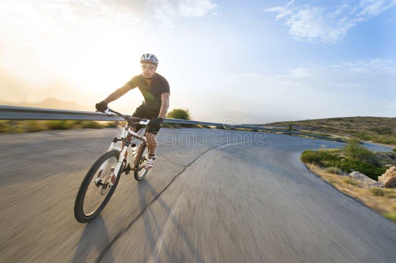 Vélo de montagne d'équitation d'homme de cycliste dans le jour ensoleillé photographie stock libre de droits