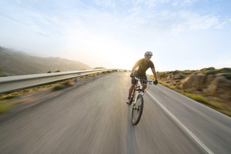 Vélo de montagne d'équitation d'homme de cycliste dans le jour ensoleillé photo libre de droits