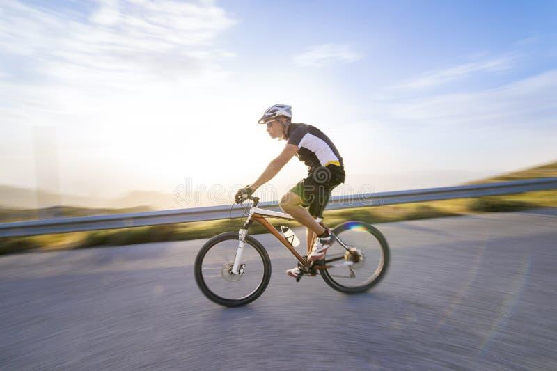 Vélo de montagne d'équitation d'homme de cycliste dans le jour ensoleillé photographie stock