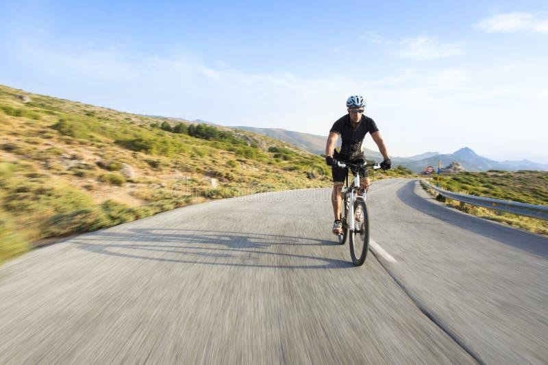 Vélo de montagne d'équitation d'homme de cycliste dans le jour ensoleillé image libre de droits