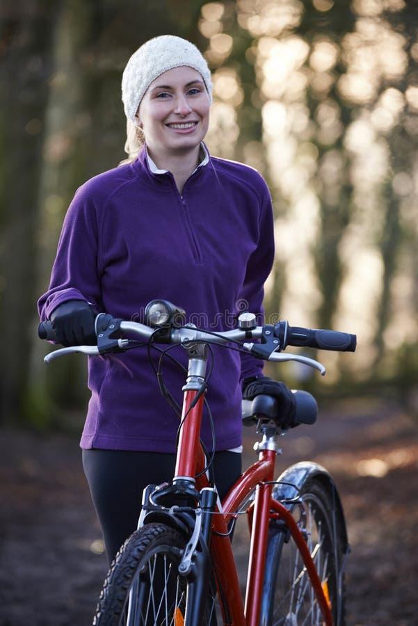 Vélo de montagne d'équitation de femme par des régions boisées photographie stock libre de droits