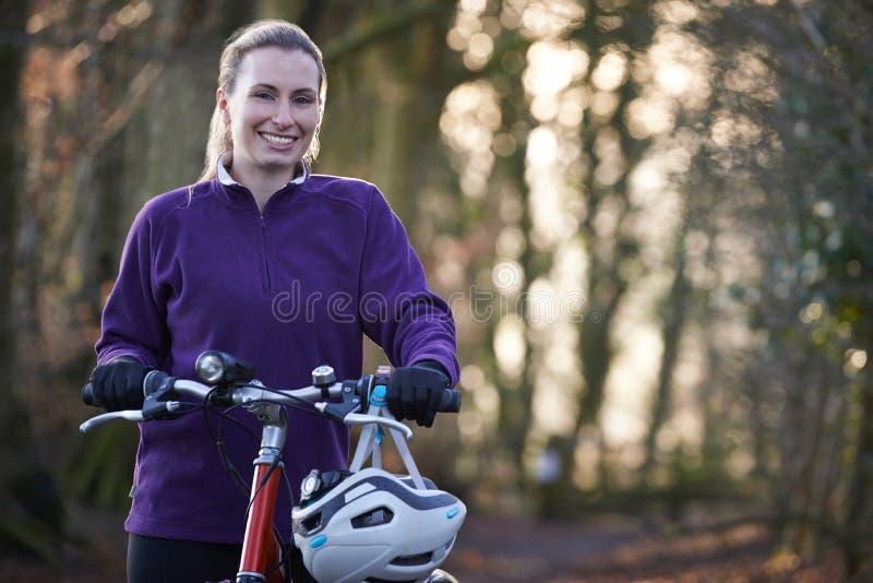 Vélo de montagne d'équitation de femme par des régions boisées photo stock