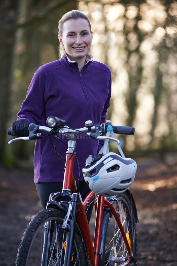 Vélo de montagne d'équitation de femme par des régions boisées photos stock