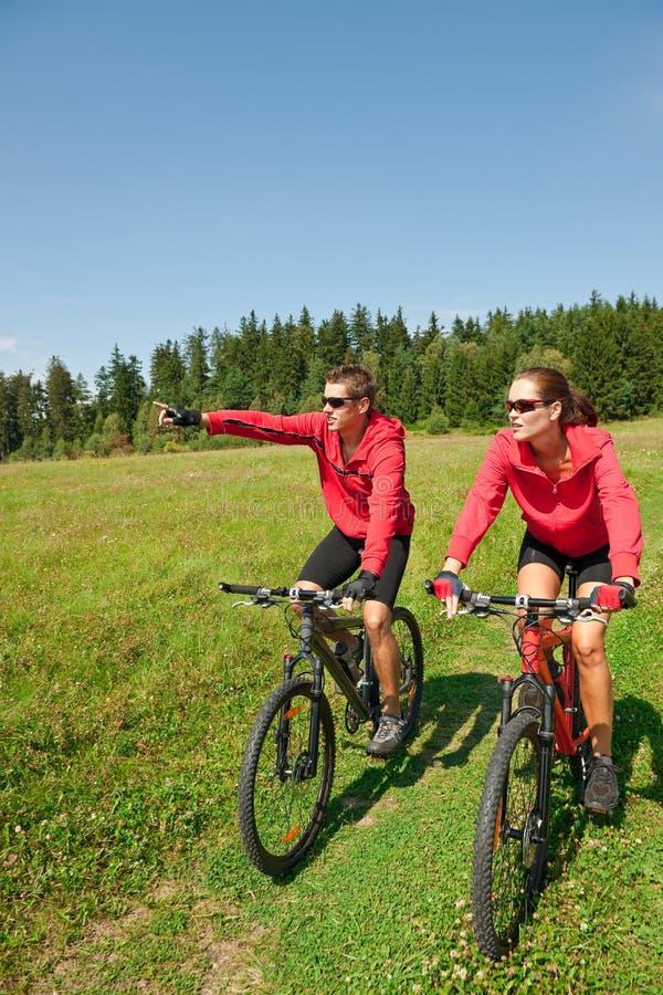 Vélo de montagne folâtre d'équitation de couples dans le pré photographie stock