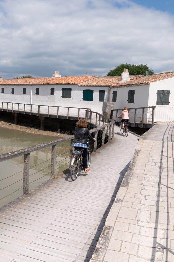 Vélo de monte de déplacement de femme sur le village de côte de plage en île re en France photographie stock