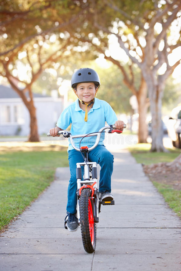 Vélo de port d'équitation de casque de sécurité de garçon photographie stock