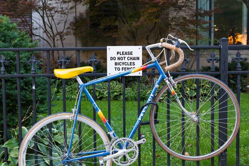 Vélo enchaîné à une barrière photos stock