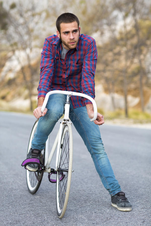 Vélo fixe de monte de sport de vitesse d'homme de cycliste dans le jour ensoleillé photo stock