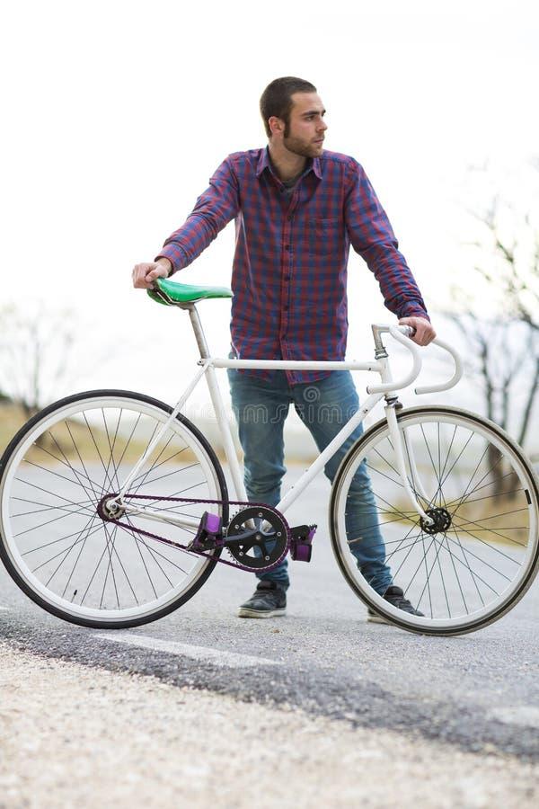 Vélo fixe de monte de sport de vitesse d'homme de cycliste dans le jour ensoleillé photographie stock